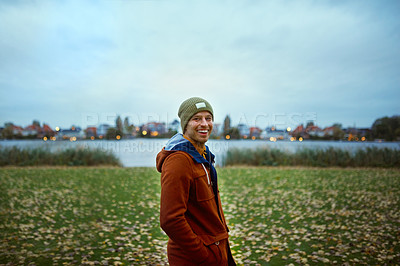 Buy stock photo Cropped portrait of a handsome young man smiling while standing in a park in late autumn