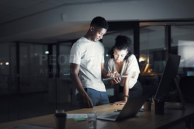 Buy stock photo Cropped shot of two confident  young designers working together late at night in their office