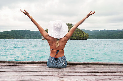 Buy stock photo Rearview shot of an unrecognizable young woman seated on a jetty while lifting her hands in the air in excitement outside next to the ocean during the day