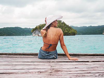 Buy stock photo Rearview shot of a cheerful young woman seated on a jetty by herself enjoying the view in front of her outside next to the ocean