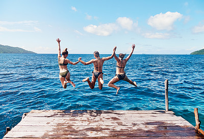 Buy stock photo Rearview shot of a group of young women jumping off a pier and into the ocean together