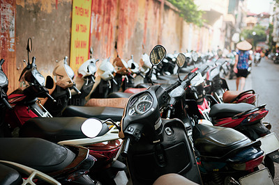 Buy stock photo Shot of a row of motorcycles lined up on a sidewalk in Vietnam