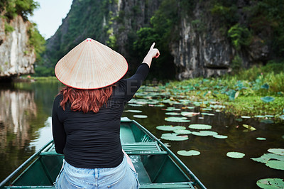 Buy stock photo Rearview shot of a young woman pointing while riding a boat down a river in Vietnam