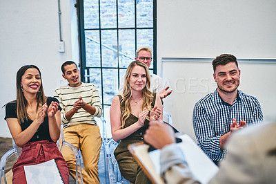 Buy stock photo Cropped shot of a diverse group of young businesspeople applauding their colleague during a seminar