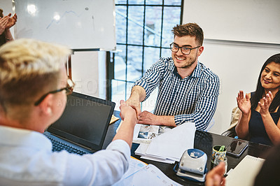 Buy stock photo Cropped shot of two handsome young businessmen shaking hands during a seminar in a modern office