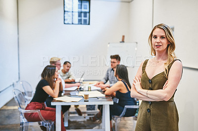 Buy stock photo Cropped portrait of an attractive young businesswoman standing in an office with her colleagues in the background
