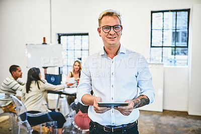 Buy stock photo Cropped portrait of a handsome middle aged businessman holding a digital tablet in an office with his colleagues in the background
