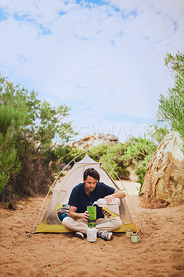 Buy stock photo Shot of a young man heating water on a camping stove in the wilderness