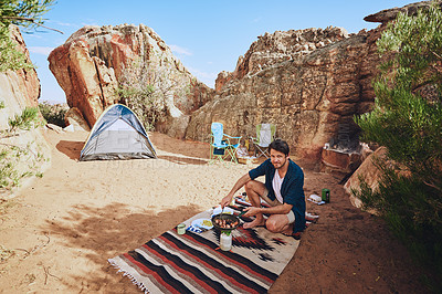 Buy stock photo Portrait of a young man preparing food while camping in the wilderness
