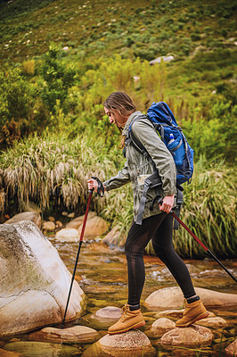 Buy stock photo Shot of a young woman walking across rocks on a lake while hiking outdoors