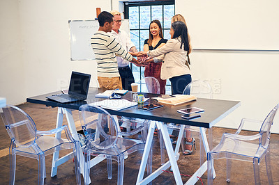 Buy stock photo Shot of a group of businesspeople joining their hands in solidarity during a meeting in a modern office