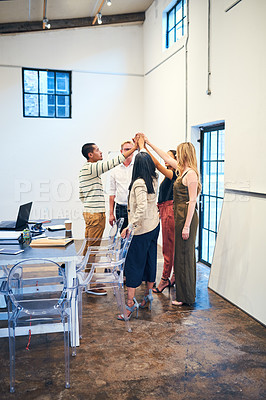 Buy stock photo Shot of a group of businesspeople giving each other a high five in a modern office