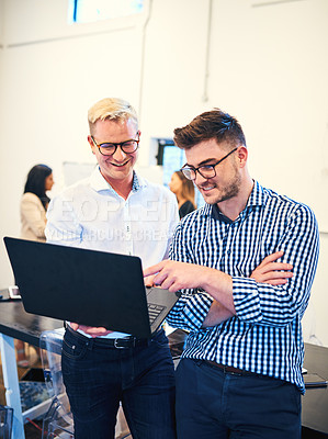 Buy stock photo Shot of two businessmen using a laptop during a meeting with colleagues in a modern office