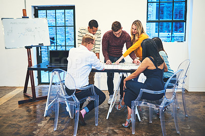 Buy stock photo Shot of a group of businesspeople designing a blueprint together in a modern office