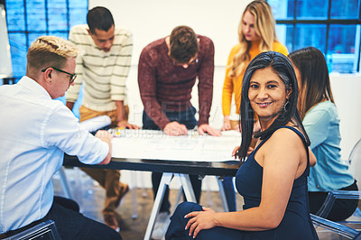 Buy stock photo Portrait of a group of businesspeople designing a blueprint together in a modern office