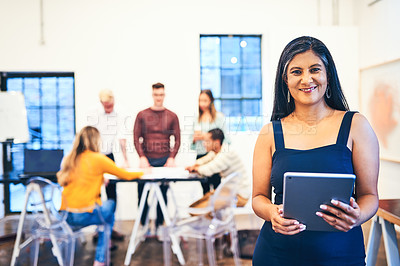 Buy stock photo Portrait of a mature businesswoman using a digital tablet with her team in the background of a modern office