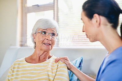 Buy stock photo Shot of a young nurse chatting to a senior woman in a retirement home