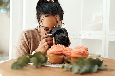Buy stock photo Cropped shot of an attractive young businesswoman using her camera to photograph cupcakes for her blog