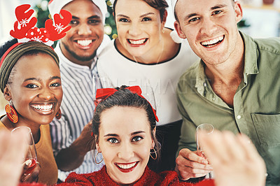 Buy stock photo Shot of a group of creative young businesspeople  taking a selfie together at their office Christmas party