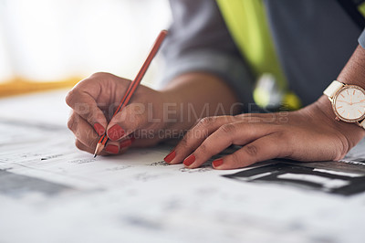 Buy stock photo Cropped shot of an unrecognizable female construction worker looking over plans on site