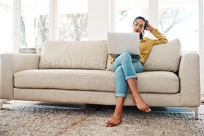 Buy stock photo Full length shot of an attractive young businesswoman sitting on her couch and blogging from her laptop while at home