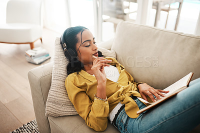 Buy stock photo Cropped shot of an attractive young businesswoman lying down on her couch and listening to music while writing notes