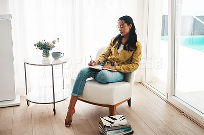 Buy stock photo Full length shot of an attractive young businesswoman sitting alone in her living room and writing notes
