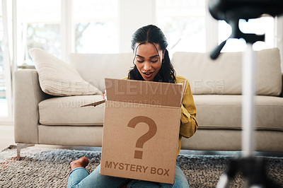 Buy stock photo Cropped shot of an attractive young businesswoman sitting in her living room and vlogging her reaction to a mystery box