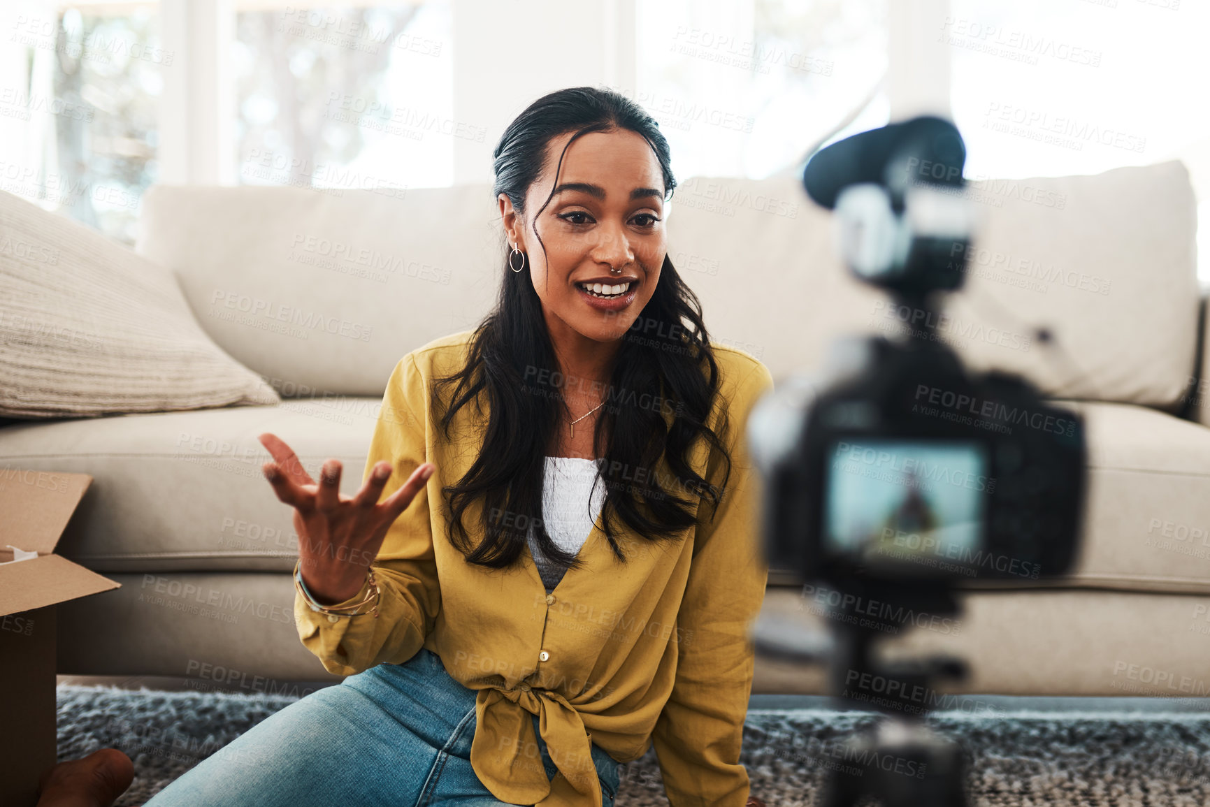 Buy stock photo Cropped shot of an attractive young businesswoman sitting in her living room and using her camera to record her vlog