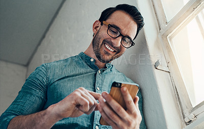 Buy stock photo Cropped shot of a handsome young businessman smiling while using a smartphone in a modern office
