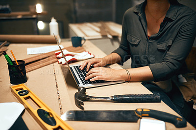 Buy stock photo Cropped shot of an unrecognizable young female carpenter working on her laptop in the workshop