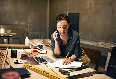 Buy stock photo Cropped shot of an attractive young female carpenter working on her laptop while talking on her cellphone inside of a workshop