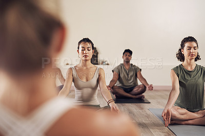 Buy stock photo Shot of a group of young people meditating and practicing yoga together inside a yoga studio