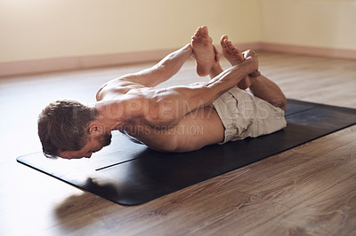 Buy stock photo Full length shot of a flexible young man stretching and practicing yoga indoors