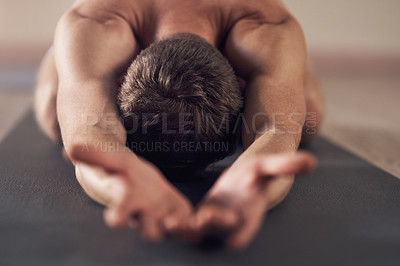 Buy stock photo Shot of an unrecognizable man stretching and practicing yoga indoors