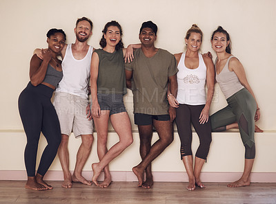 Buy stock photo Full length shot of a group of active young people posing together against a wall in yoga class