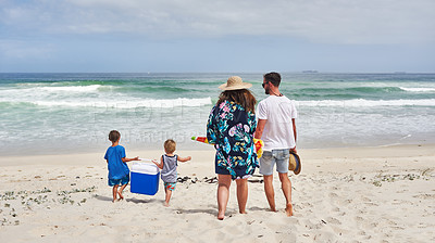 Buy stock photo Rearview shot of two adorable little boys carrying a cooler box with their parents at the beach