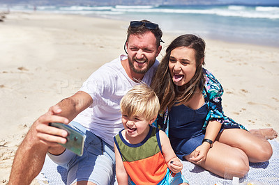 Buy stock photo Shot of a happy family taking selfies together at the beach
