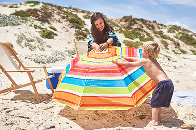 Buy stock photo Shot of a mother and her little son setting up an umbrella at the beach