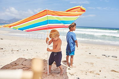 Buy stock photo Shot of two little boys putting up an umbrella at the beach