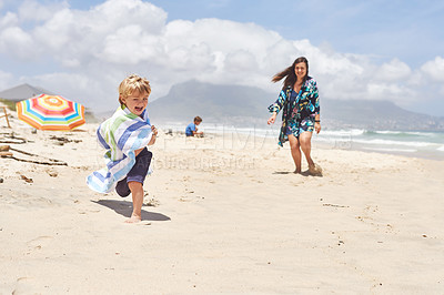 Buy stock photo Shot of an adorable little boy playing with his mother at the beach