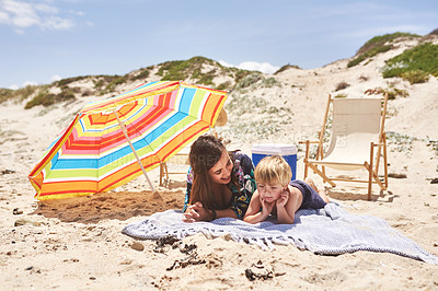 Buy stock photo Shot of a mother and her little son lying on a blanket at the beach
