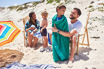 Buy stock photo Shot of a father wrapping his little son in a towel at the beach with their family in the background