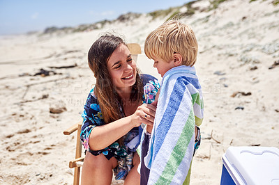 Buy stock photo Shot of a mother wrapping her little son in a towel at the beach