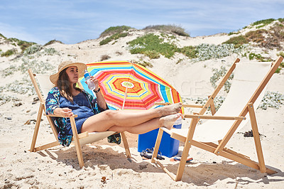 Buy stock photo Shot of a young woman drinking water while relaxing on a deck chair at the beach