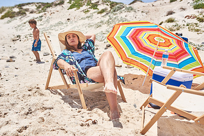 Buy stock photo Shot of a mother sleeping on a deck chair at the beach with her son in the background