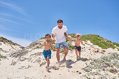 Buy stock photo Shot of a father bonding with his two little sons at the beach