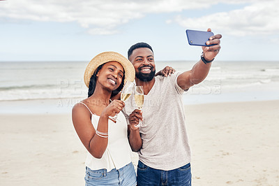 Buy stock photo Shot of a happy young couple taking a selfie while enjoying themselves at the beach