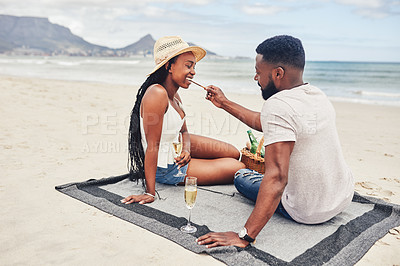 Buy stock photo Shot of a happy young couple having champagne while relaxing on the beach