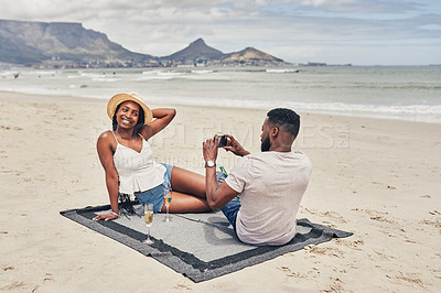 Buy stock photo Shot of a man taking a picture of his girlfriend while relaxing on the beach